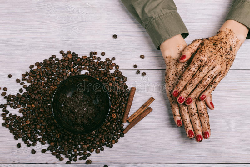 Female hands with red nail polish and applied coffee scrub on th. E table, top view royalty free stock image
