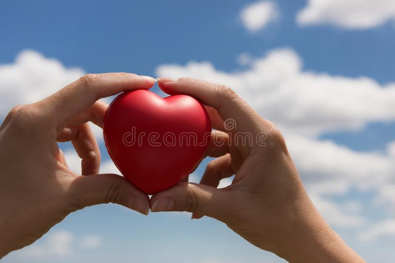In female hands a red volumetric heart, as a symbol of life and love, against the blue sky with clouds royalty free stock photo