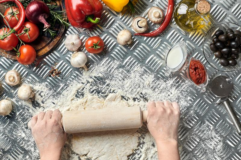 Female hands roll out dough on metal background, close up. Chef makes dough. Table with vegetables and kitchenware stock photo