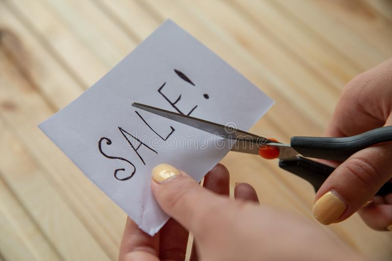 Female hands is scissoring note with inscription Sale on the wooden background. Buy Nothing Day stock images