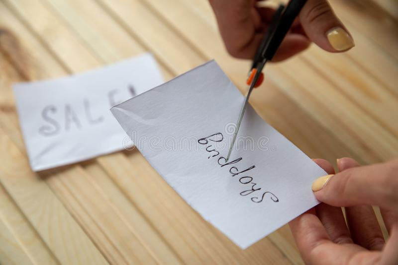 Female hands is scissoring note with inscription Shopping on the wooden background.  On the background is note with inscription Sa stock photo