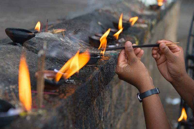 Female hands set fire to fragrant sticks in the temple offerings. Place stock photography