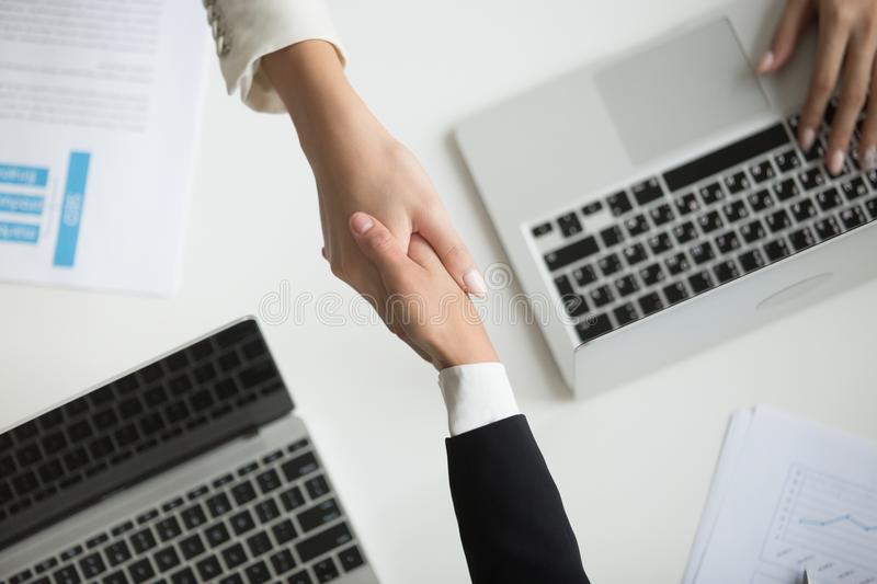 Female hands shaking at meeting making deal, top closeup view. Female hands shaking at meeting making partnership deal, businesswomen handshaking as concept of royalty free stock images