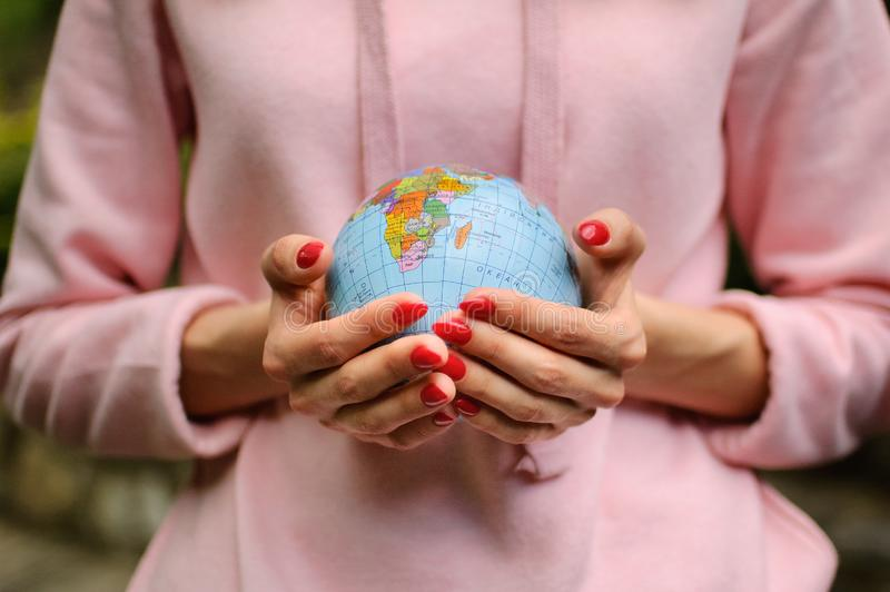 Female hands with a small globe with Ukrainian names and Cyrillic letters on it. African continent and Indian Ocean are stock photography