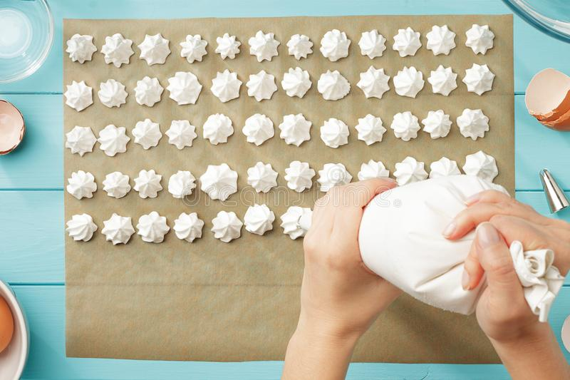 Female hands squeeze whipped cream on baking paper. royalty free stock photo