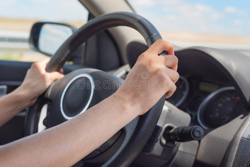 Female hands on the steering wheel of a car while driving royalty free stock image