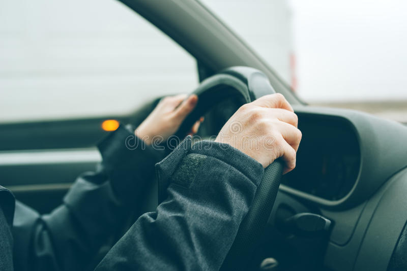 Female hands on steering wheel. Woman driving car on cold winter afternoon royalty free stock image