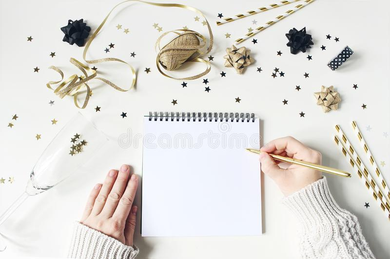 Female hands in sweater and writing. New year resolution, wish list concept. Blank paper letter mockup. Golden party. Decoration, confetti and wine glass on stock photos