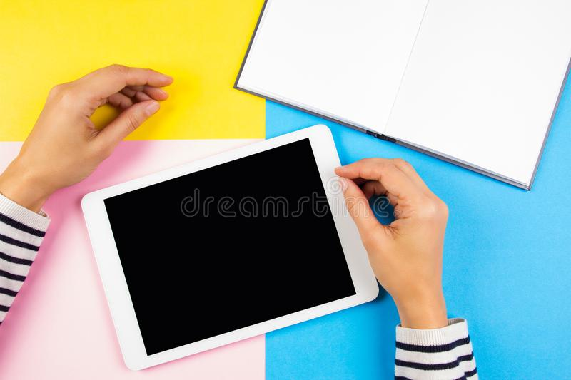 Female hands with tablet computer and open notebook over yellow, blue and pink background. stock image