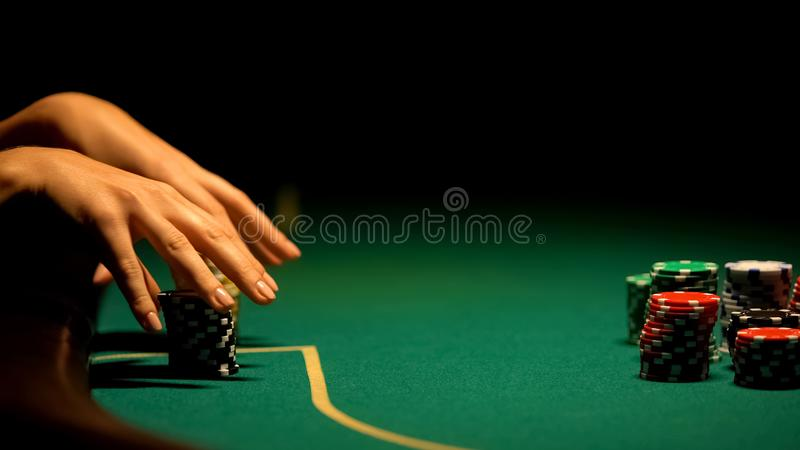 Female hands taking casino chips, strategy and betting all-in, bluffing, closeup. Stock photo royalty free stock photos