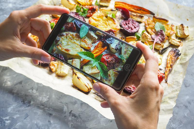 Female hands taking photo of food with mobile phone. Baked vegetables on parchment. royalty free stock photography