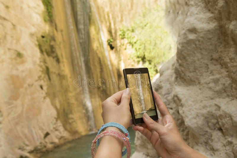 Female hands taking a photo of waterfall with a smartphone stock photo