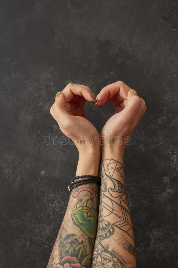 Female hands with tattoos in shape of heart. Female hands with tattoos in the shape of heart on a dark background.Flat lay royalty free stock photo