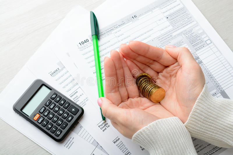 Female hands and tax form. Coins in female palms and tax form on the table stock photos