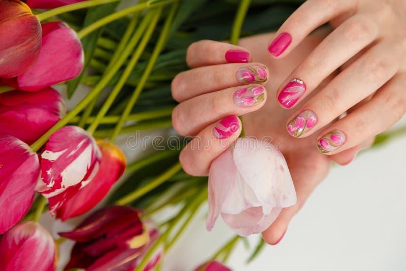 female hands tender spring manicure holding pink fresh tulip flowers background nail art gel nails polish design 200676391