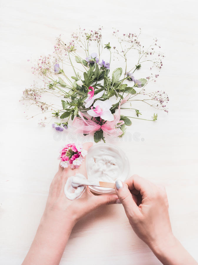 Female Hands test lubricate herbal dermatology cosmetic hygienic cream for beauty and skincare with flowers and herbs bunch on whi. Te wooden background, top royalty free stock images
