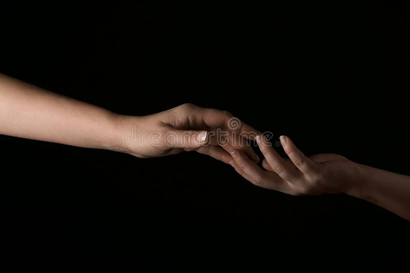 Female hands touching fingers on dark background stock photography