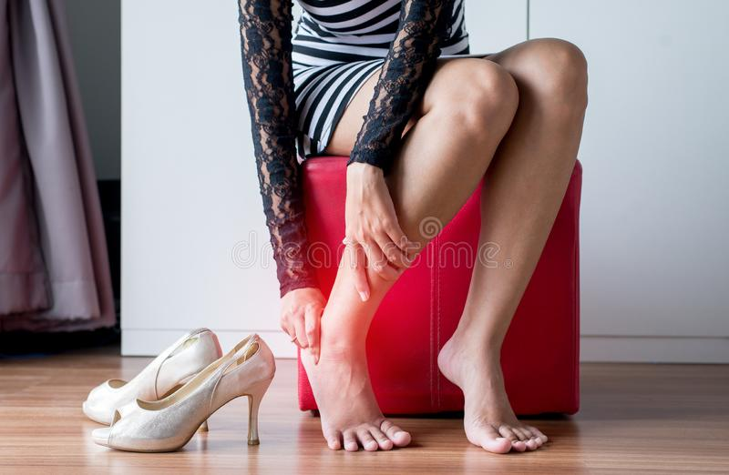 Woman hands touching her ankle and calf muscle because suffering from foot inflammation pain,Close up. Female hands touching her ankle and calf muscle because royalty free stock images