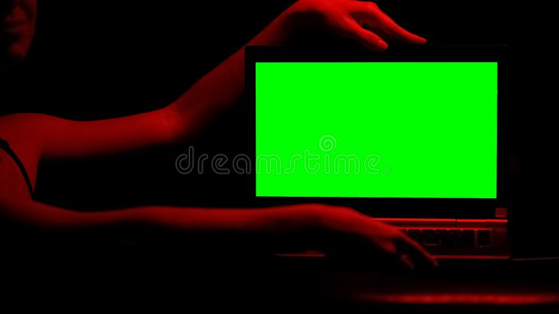 Female hands touching laptop, red illumination, concept of adult sites, app stock photo