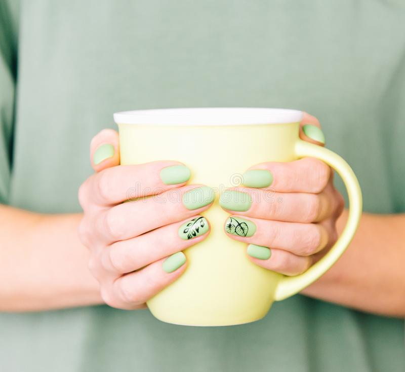 Female hands with stylish green manicure holding a cup. stock photo