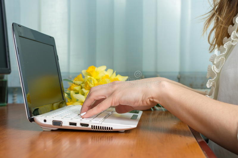 Female hands typing at a lap top stock images