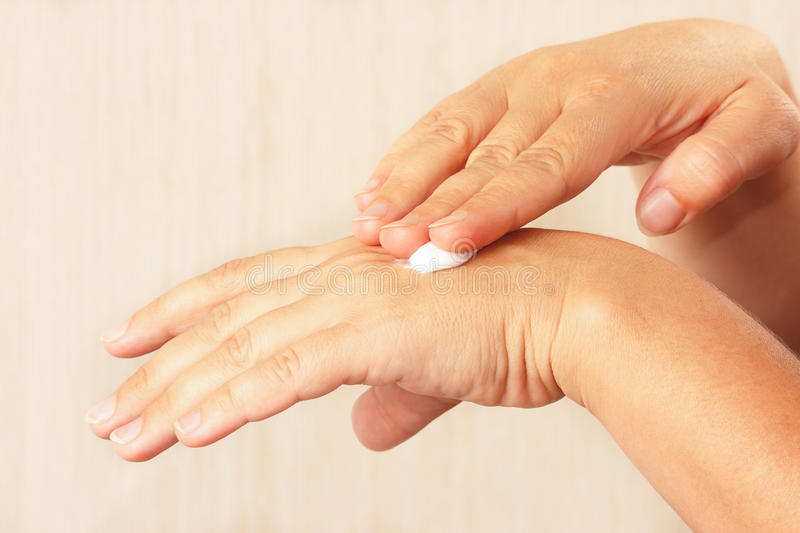 Female hands using anti-aging skin cream royalty free stock photography