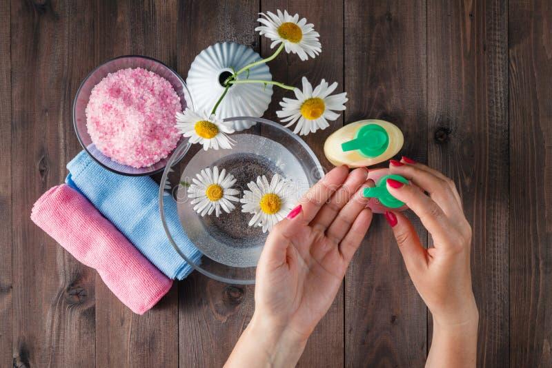 Female hands using dispenser with liquid soap stock photos