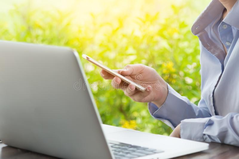 Female hands using modern smart phone while working at office with computer, businesswoman typing text message on her cellphone royalty free stock image