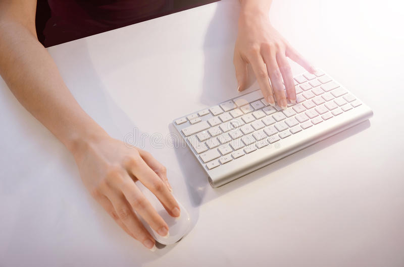 Female hands using mouse and keyboard royalty free stock photo