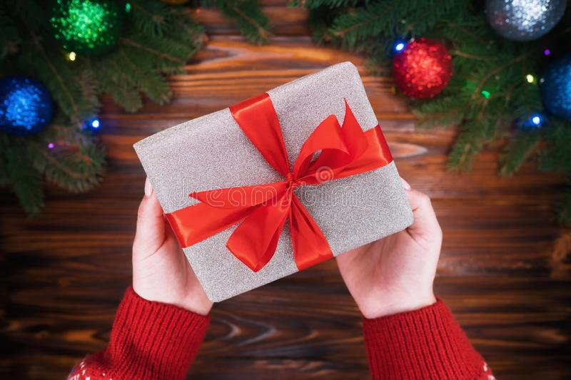 Female hands in warm red sweater giving present in silver paper with red bow. Wooden vintage table with Christmas royalty free stock photography