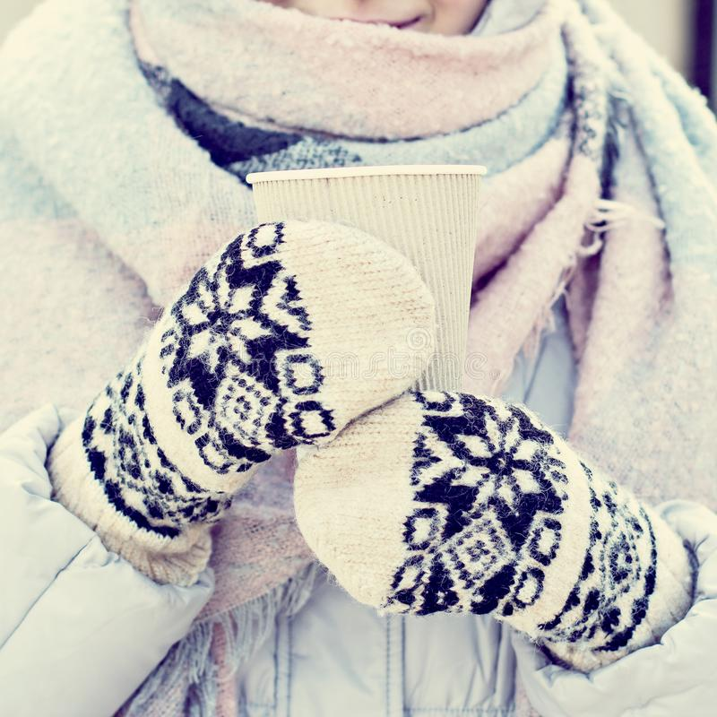 Female hands in white and black mittens holding steaming cup royalty free stock photos