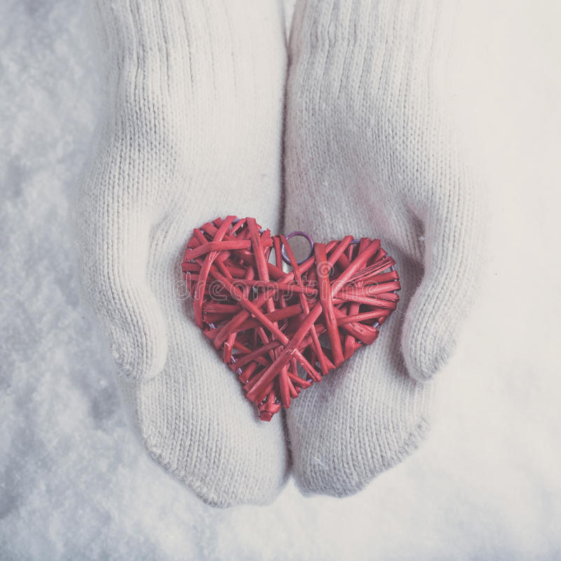 Female hands in white knitted mittens with a entwined vintage romantic red heart on a snow. Love and St. Valentine concept. Female hands in white knitted royalty free stock photos