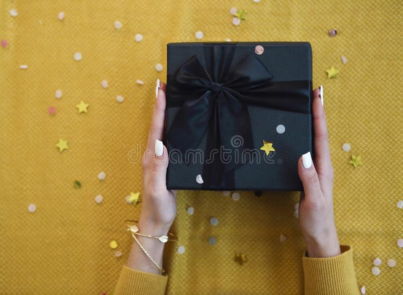 Female hands with a white manicure holding gift box for the Christmas or New Year. Christmas layout royalty free stock image