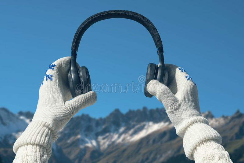 Female hands in the winter mittens with a headphones in the snow mountains. Lake in the Alps at snow frozen day. stock photo