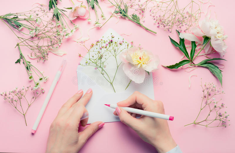 Female hands write with pencil on opened envelop with flowers arrangement . Florist decoration equipment on pink table background stock photos