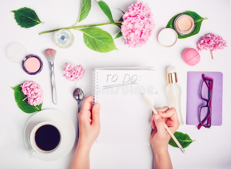 Female hands write To do list on the white working place with female accessories, cup of coffee, notebook, glasses, and wisteria f royalty free stock image