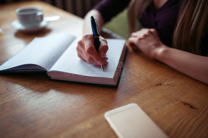 Female hands writing in notebook closeup. Female hands writing in notebook on the table closeup royalty free stock images