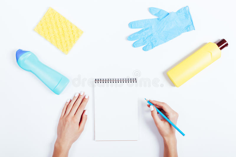 Female hands writing in notepad, yellow and blue bottle of deter. Gent and sponge on white background, top view stock images