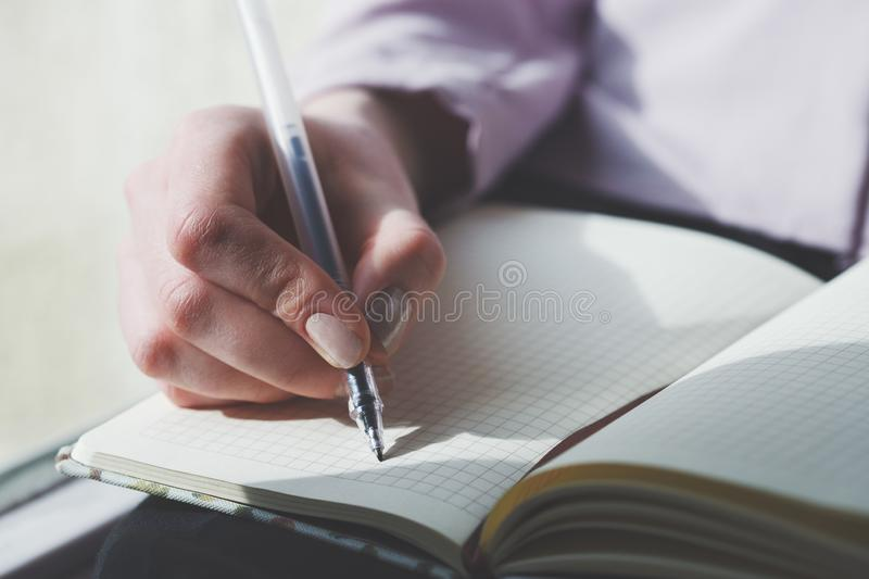 Female hands writing notes on notebook stock photo