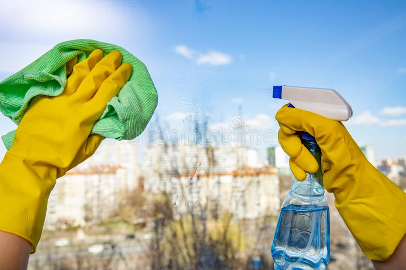 Female hands in yellow gloves cleaning window with green rag and spray detergent. Spring cleanup, housework concept. The Female hands in yellow gloves cleaning stock images