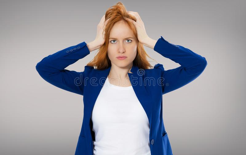 Female headache isolated on gray background - suffering business woman, hard work in company royalty free stock photography