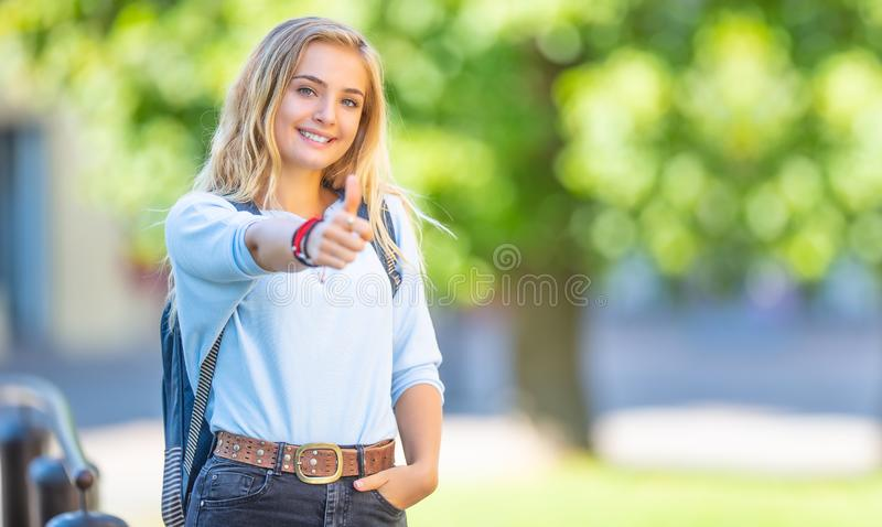 Female high school student with schoolbag. Portrait of attractive young blonde girl showing thumbs up stock image