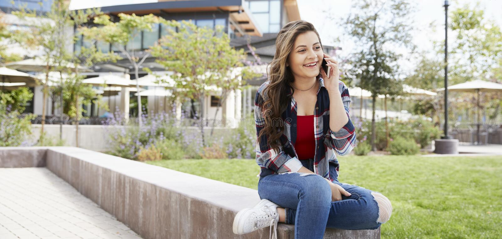 Female High School Student Talking On Mobile Phone Outside College Buildings royalty free stock image