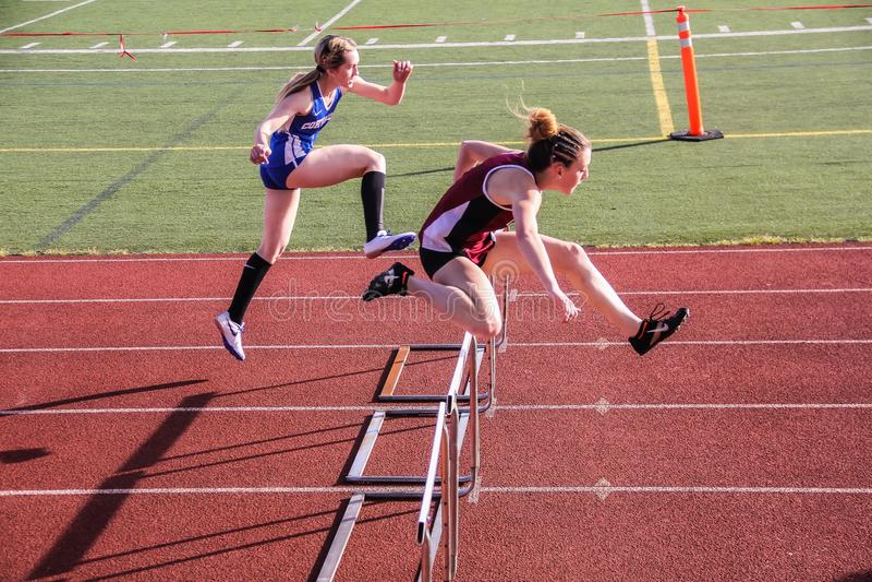 Female high school track athletes clear hurdles in 300 meter hurdle race. Corvallis, Oregon, April 6, 2016: Female high school athletes clear hurdles in 300 royalty free stock image