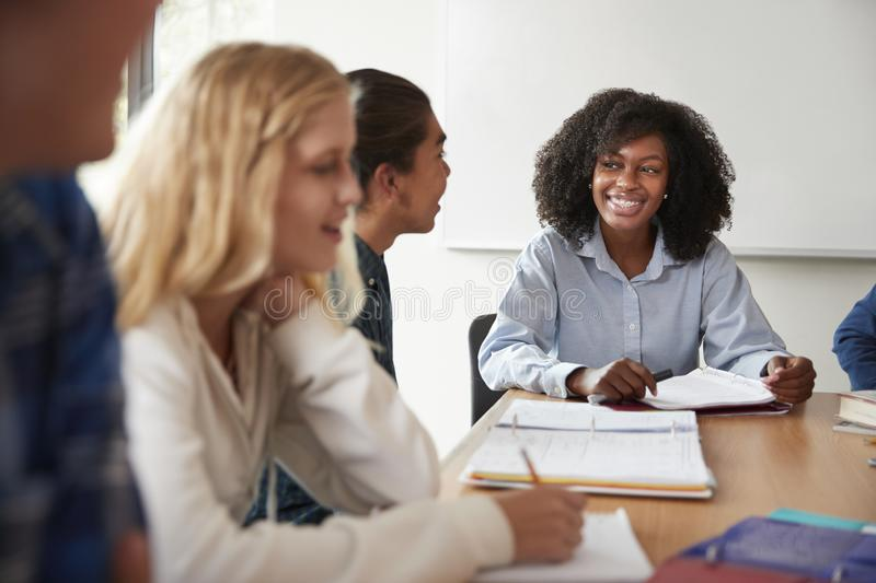 Female High School Tutor Sitting At Table With Pupils Teaching Maths Class stock image
