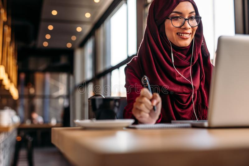 Female in hijab at cafe having video conference on her laptop royalty free stock photos