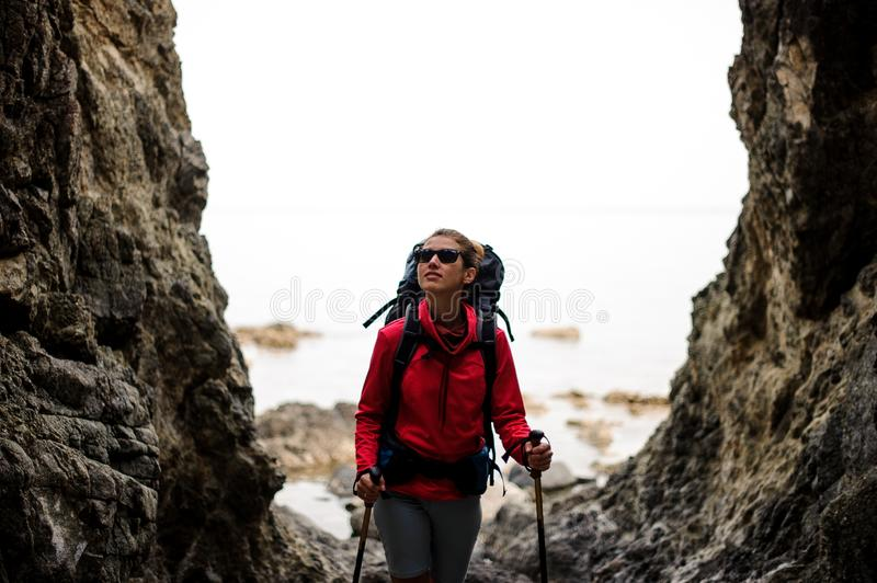 Female hiker with backpack standing between cliffs royalty free stock images