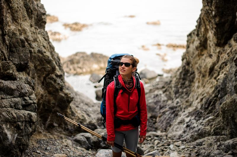 Female hiker with backpack stands between cliffs royalty free stock photos