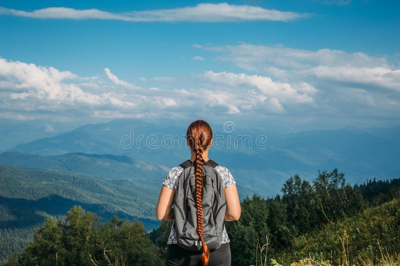 Female hiker with backpack stands on top of mountain and looks to valley, mountain landscape stock photo