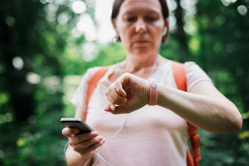 Female hiker checking fitness tracker wristband data stock photos